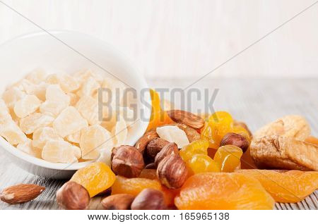 Dried fruits and nuts on a wooden background