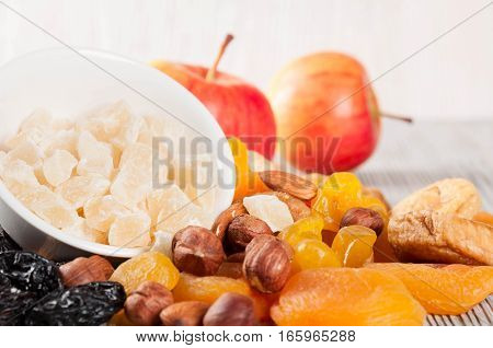 Dried fruits red ripe apples and nuts on a wooden background
