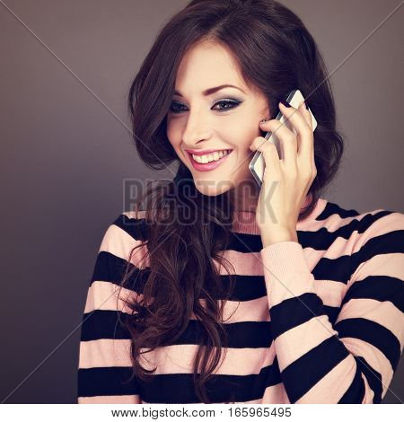 Beautiful Makeup Happy Woman Talking On Mobile Phone On Grey Background With Toothy Smiling. Curly H