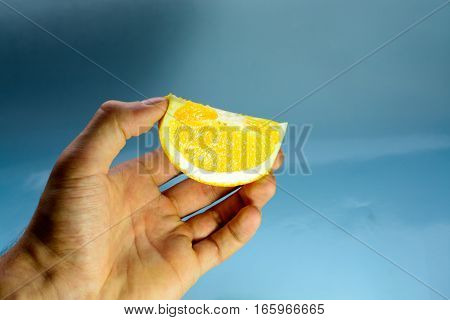 hand with a slice of orange on a blue background