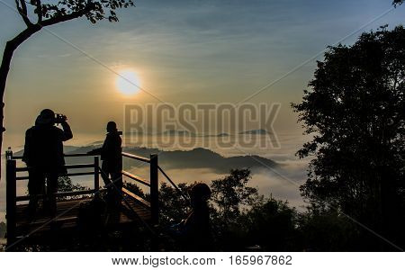 Silhouettes of tourists on viewpoint with the mountain in morning.