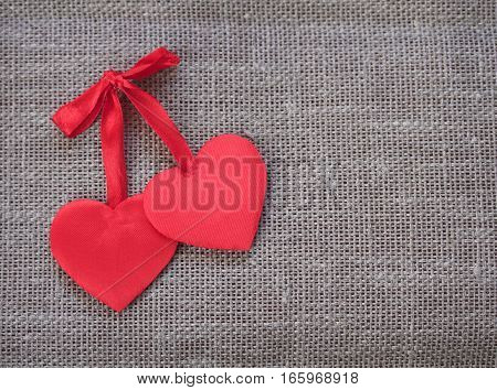 two red satin hearts lie together on a linen background