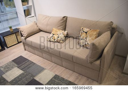 Stylish beige sofa with lots of pillows. Furniture