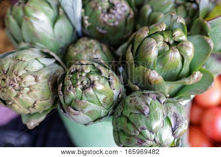 Fresh artichokes for sale at farmer's market. Horizontal. Above view. Daylight. Close up.