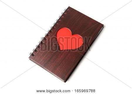 wooden texture notebook with red heart on white background.