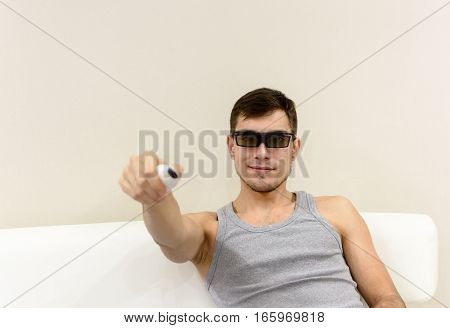 young man in 3D glasses at home on a white sofa