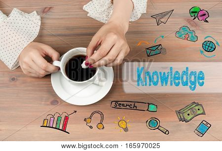 Knowledge. Coffee cup top view on wooden table background.