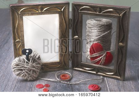 White photo frame on wooden table over grunge background, Valentine concept, Key from the heart