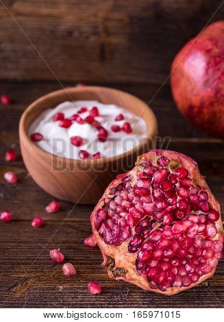Sliced red pomegranate on wooden desk with yogurt in behind.
