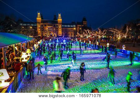 AMSTERDAM THE NETHERLANDS - JANUARY 12 2017: Many people skate on winter ice skating rink at night in front of the Rijksmuseum a popular touristic destination in Amsterdam The Netherlands.