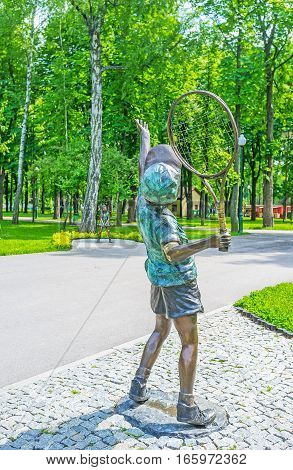 KHARKOV UKRAINE - MAY 20 2016: The bronze sculpture of a young tennis player serving the ball to his partner the Sculpture Garden of Gorky Park on May 20 in Kharkov.