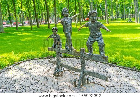KHARKOV UKRAINE - MAY 20 2016: The bronze sculpture of the three little friends walking on the old wooden fence in the Sculpture Garden in Gorky Park on May 20 in Kharkov.