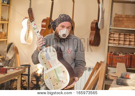 GRODNO BELARUS - JANUARY 18 2017. Serious professional guitar-maker going with unfinished guitar at workshop.