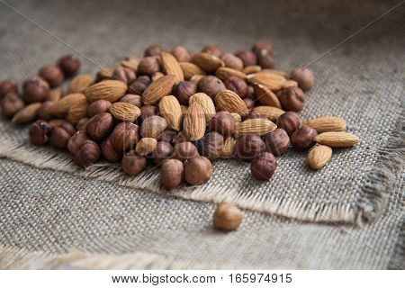 pile of almond nuts and hazelnuts on a gray cloth of burlap