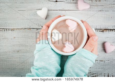 Girl drinking hot chocolate with marshmallows in the shape of hearts Valentine's Day celebration hands in the picture top view copy space