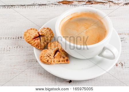 Idea for the celebration of Valentine's Day: big cherry pie and one-bite cherry pies in the form of hearts cup of coffee top view