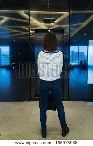 Brunette woman waiting for elevator, view from the back