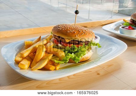 Burger in sesame bun with french fries