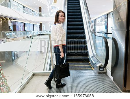 Woman standing near an escalator in a mall