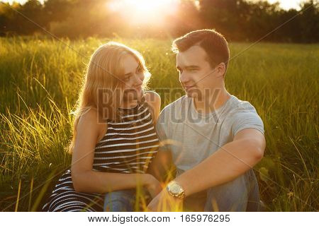 Happy couple outdoor. Smiling couple relaxing on the green grass. Girl and boy over nature green background. Good relationships. Romantic concept. Summer time. Relaxation outdoor. Couple in love