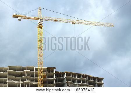 Big yellow hoisting tower crane above top of construction building over stormy sky