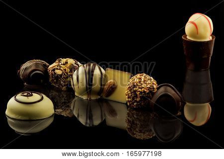 Chocolate candies assortment on black background with reflection.