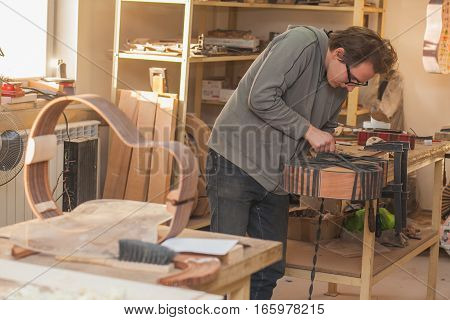 GRODNO BELARUS - JANUARY 18 2017. Serious professional guitar-maker working with unfinished guitar at workshop.