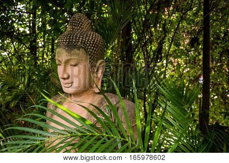 The stone Buddha statue in forest background.