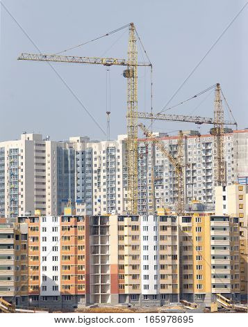 Yellow hoisting tower cranes construction new city buildings and residential houses