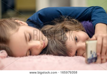 Two little girls with smartphone lying on bed at home and playing mobile games