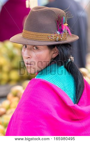 July 24, 2016 Alausi, Ecuador: portrait of an indigenous kichwa woman dressed traditionally wearing a feather decorated felt hat outdoors