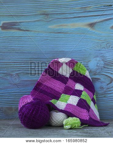 Pink violet magenta white and green plaid and balls. Cotton yarn for knitting crochet. The beginning of bright plaid checkered knitted blanket and crochet hooks