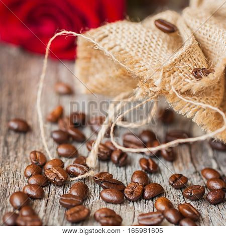 Roasted coffee beans on a brown wooden background with coarse roughly woven burlap and red rose, grunge texture. Place for your text. Vintage, rustic background