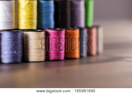 Colorful cotton reels lined and stacked together in a row and viewed at an angle to create shallow depth of field