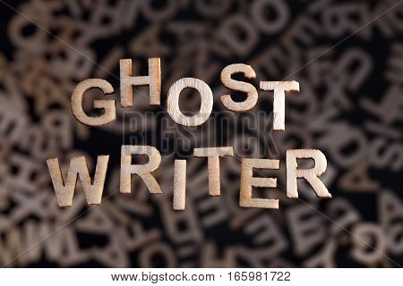Ghostwriter text in wooden letters floating above random letters out of focus