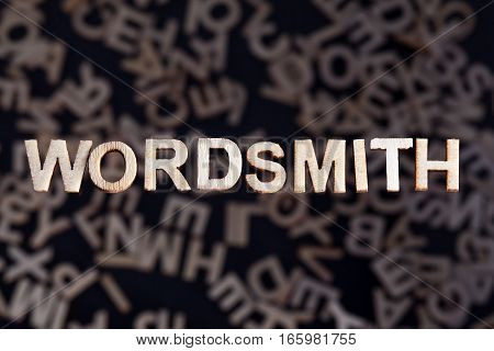 Wordsmith wooden letters created in wood floating above random letters below out of focus on a black background