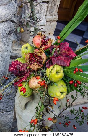 Autumn still life - a vase with flowers and fruits