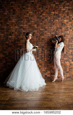 Young sexy photographer is taking pictures the bride in the studio