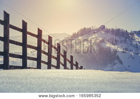 Beautiful countryside landscape with wooden fence and sunrise light over snow covered hills and valleys in Rucar-Bran pass Romania. Selective focus.