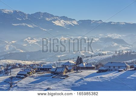 Picturesque rural landscape with traditional Romanian hamlet in the valley of Bucegi mountains on a cold winter afternoon Pestera village Bran-Rucar pass Transylvania region Romania.