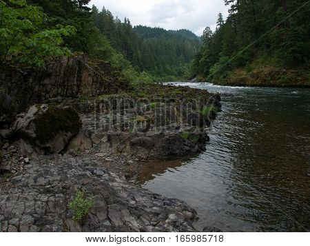 Rugged rocks formed into natural steps with trees bushes and moss make up the banks of the North Umpqua River in Douglas County in Western Oregon on a summer day.