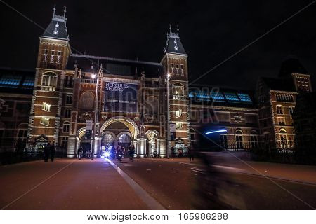 AMSTERDAM NETHERLANDS - JANUARY 07 2017: Moving silhouettes of cyclists and passersby near Rijksmuseum (national museum dedicated to arts and history). January 07 2017 in Amsterdam Netherlands.