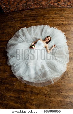 Young sexy bride in the studio is lying on the wooden floor