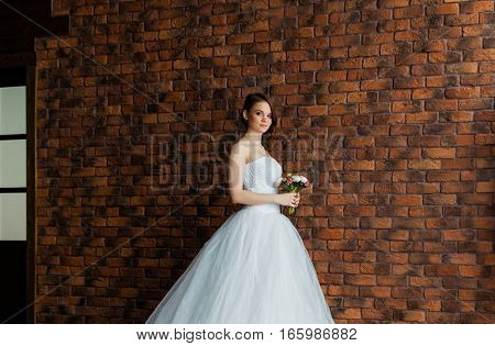 Young sexy bride in a studio standing next to the wall