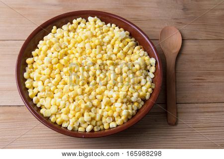 Frozen Corn In A Bowl With A Wooden Spoon