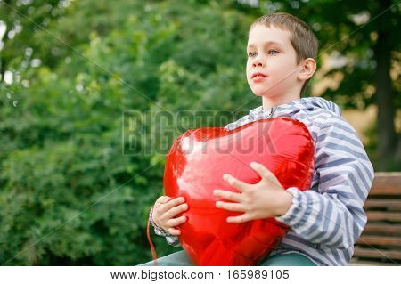 boy hugging a big red heart balloon. Valentine's day. empty space for your text