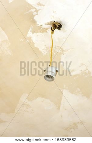 Ceramic cartridge for light bulb hangs on yellow wire from ceiling