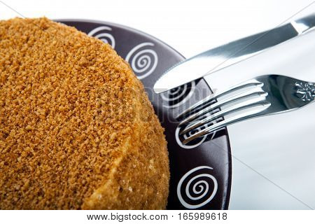 whole cream cake on the plate and fork and knife close up