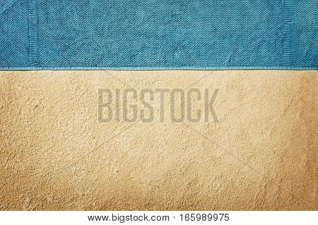 Top view of sandy beach with towel frame. Background with copy space and visible sand texture. Top border made of towel