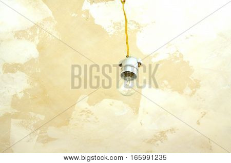 Electric bulb in white ceramic cartridge hangs from repaired ceiling